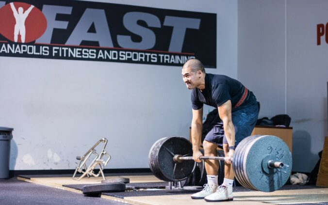 Kevin Phengthavone 500 pound deadlift on platform with IFAST logo in background