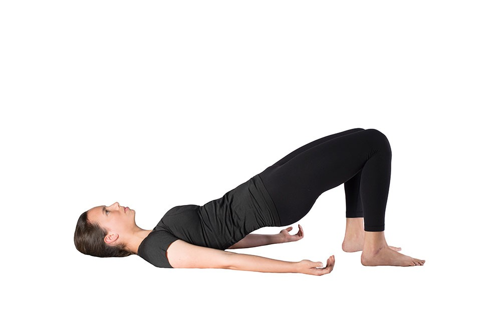 Woman lying supine with knees bent, feet flat, and hips bridged up in the air