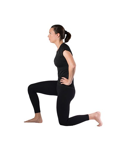 Woman doing quad stretch while kneeling on one knee with hands on hips