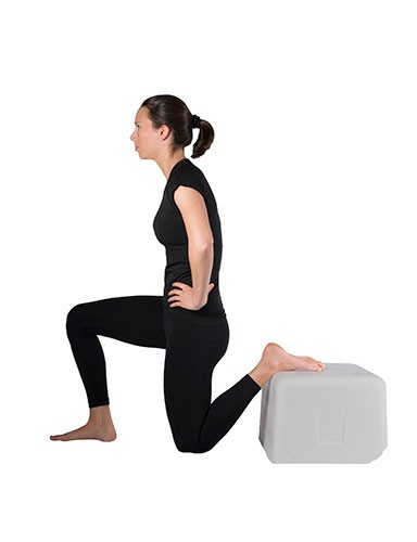 Woman doing quad stretch while kneeling on one knee with hands on hips with back foot elevated.
