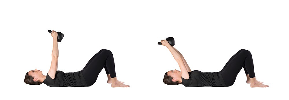 Woman lying supine with kettlebell in hands, arms straight up perpendicular to the ground. Second photo shows same woman with the kettlebell hover over her head, arms still straight but now angled back toward her head.