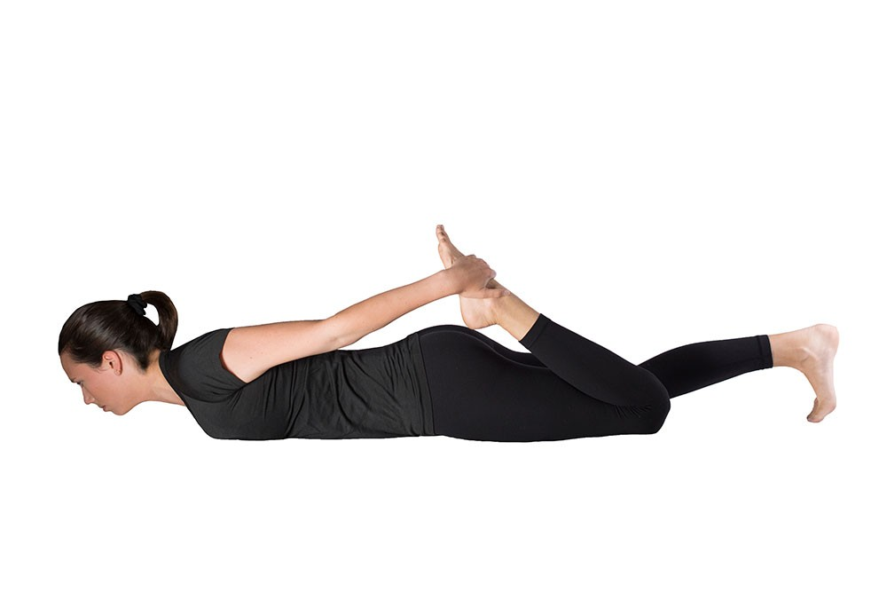 Woman doing quad stretch lying prone with left hand grabbing left foot to pull to butt