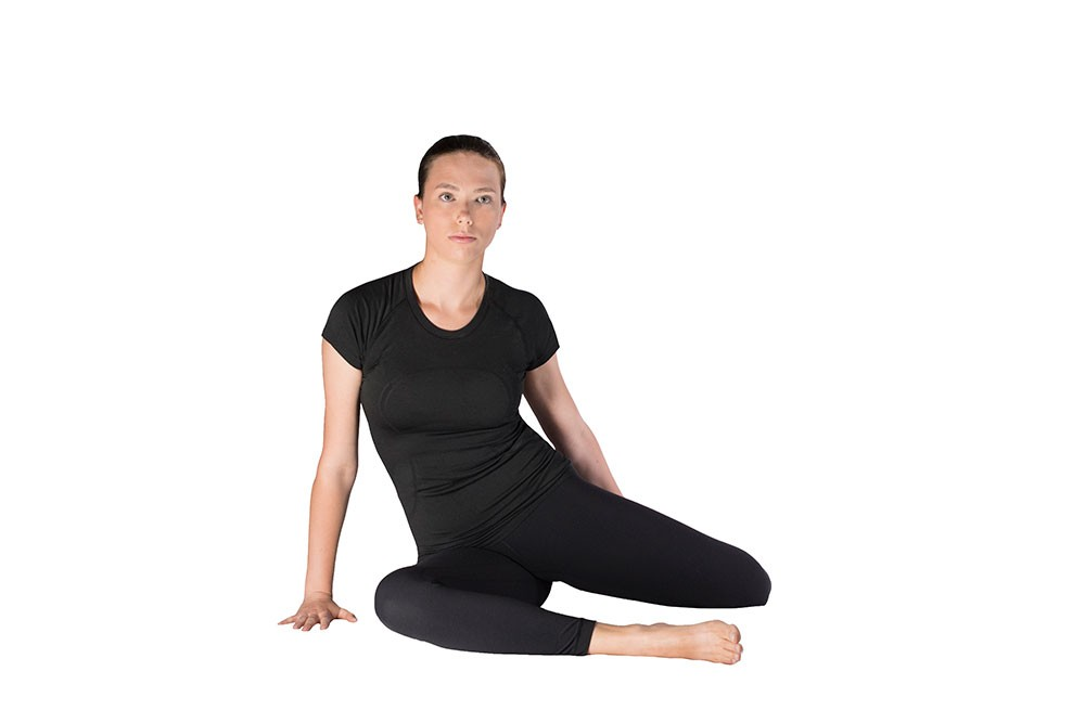 Woman doing quad stretch sitting on side of right butt while bent legs are pointing left. Left hand is behind her, grabbing left ankle and pulling to butt
