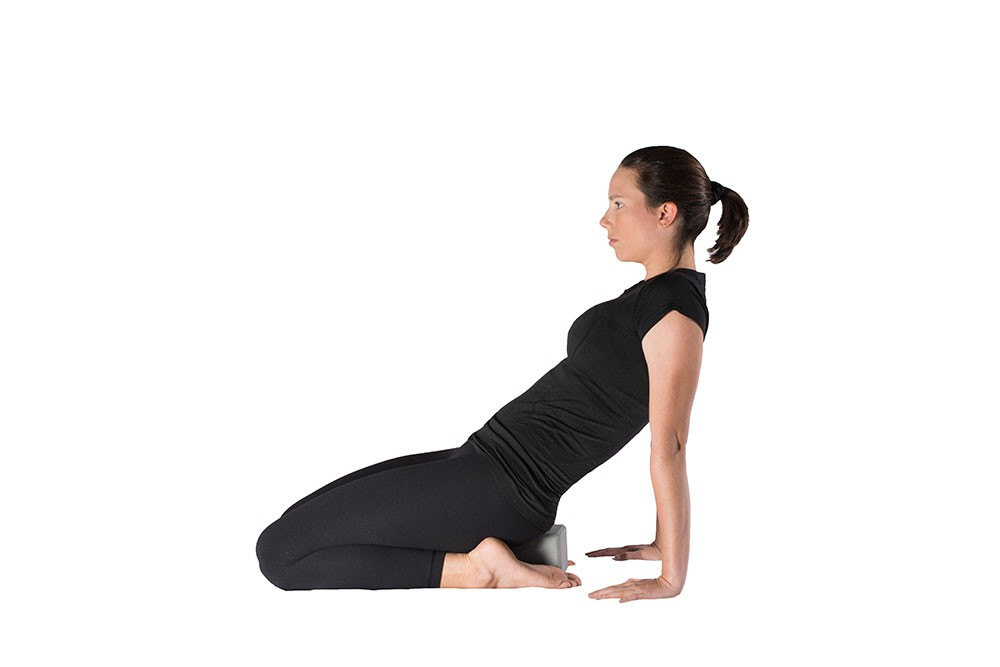 Woman doing quad stretch while kneeling, sitting back onto a yoga block resting on the ground between her feet. Torso is leaning backward with weight on hands and fingers pointed forward