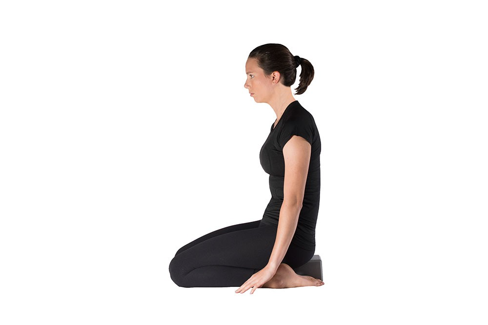 Woman doing quad stretch while kneeling, sitting back onto a yoga block resting on the ground between her feet