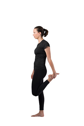 Woman doing quad stretch while standing, using hand to pull left foot to the butt