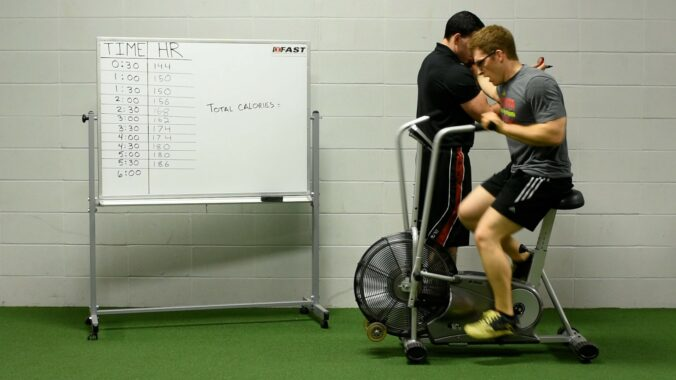 Man on fan bike with labored breathing next to a whiteboard with a data table listing heart rates at thirty second intervals